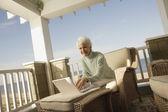 Senior woman using a laptop on the porch — Stock Photo
