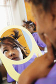Young woman examining herself in the mirror — Stock Photo