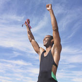 African male athlete cheering while holding medal — Stock Photo
