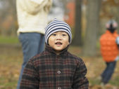 Young Asian child in hat and coat at the park — Stock Photo