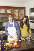 Young Hispanic couple chopping vegetables — Stock Photo