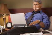 Businessman using a laptop in his hotel room — Stock Photo