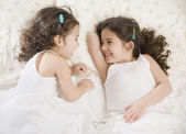 Two young Hispanic sisters giggling in bed — Stockfoto
