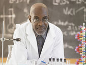African male science teacher in front of the blackboard — Stock Photo