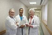 Three doctors standing in hospital hallway — Stock Photo