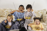 Group of children eating and watching television — Stock Photo