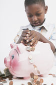 Young African boy putting money in a piggy bank — Stock Photo