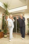 Senior Asian couple doing Tai Chi indoors — Stock Photo