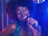 Young woman singing into a microphone — Stock Photo