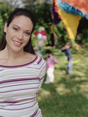 BLD021588Young woman smiling for the camera at a child's birthday party — Foto Stock