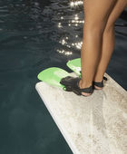 Little girl in flippers standing on the end of a diving board — Stock Photo