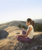Middle-aged woman meditating outdoors — Stok fotoğraf