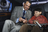 Affärsman som visar sin son en gadget — Stockfoto