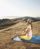 Sênior mulher meditando sobre um tapete de ioga ao ar livre — Foto Stock