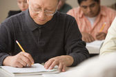 Mature man writing during class — Stock Photo