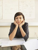 Businesswoman leaning over a desk — Stock Photo