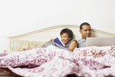 Couple using a laptop in bed — Stockfoto
