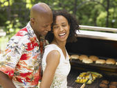 Couple laughing as they barbecue together — Stock Photo