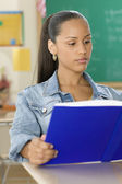 Female Dominican teenager reading a textbook in classroom — Stock Photo