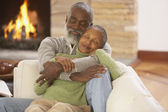 Casal africano sênior, abraços no sofá — Foto Stock
