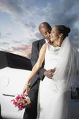 Newlyweds hugging by limo — Stock Photo