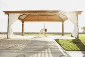 Woman doing yoga at beach resort — Stock Photo