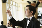 Upscale male waiter examining glass — Stock Photo