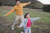 Asian father playing with young daughter in the countryside — Stock Photo