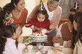 Hispanic girl blowing out her birthday candles — Stock Photo