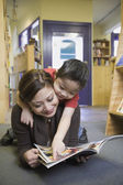 Mother and young son reading book at bookstore — Stock Photo