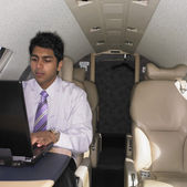 Young Indian businessman working on laptop inside airplane — Stock Photo