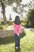 Rear view of young Asian girl standing in the sunlight — Stock Photo