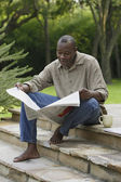 Man reading newspaper outdoors — Stock Photo