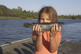 Young girl holding a freshly-caught fish — Stock Photo