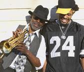 молодых африканских человек смеется рядом старших африканских человек с трубой — Стоковое фото