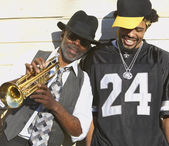 Joven africana riendo junto a un hombre africano senior con trompeta — Foto de Stock