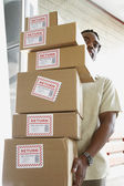 African man carrying returned packages — Stock Photo
