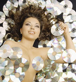 Young semi-nude woman lying amongst CDs — Stock Photo