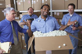 Businessman with male warehouse workers joking around — Stock Photo