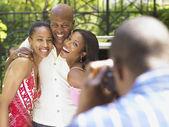 Family smiling as man take a photo — Stock Photo