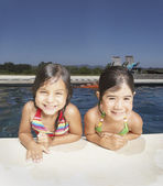 Young girls smiling for the camera by a swimming pool — Stock Photo