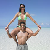 Man carrying his girlfriend on his shoulders at the beach — Stock Photo