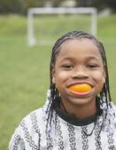 Young girl wearing orange peel over her teeth — Stock Photo