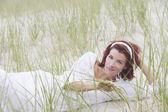 Jonge vrouw die lacht voor de camera op het strand — Stockfoto
