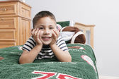 年轻的男孩微笑着为他的床上的摄像头 — 图库照片