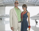 Couple hugging in airplane hanger — Stock Photo