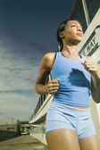 Female athlete running in urban surroundings — Stock Photo
