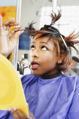 Young woman checking her hair in beauty salon — Stock Photo