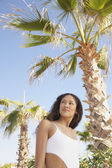 Hispanic woman in bathing suit next to palm trees — Stock Photo