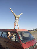 Man doing a handstand on car roof — Stock Photo